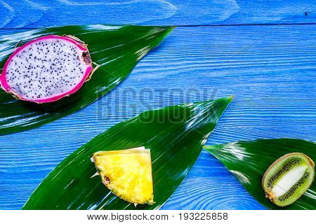 Pieces of exotic fruits. Dragonfruit, pineapple and kiwi on blue wooden background top view.