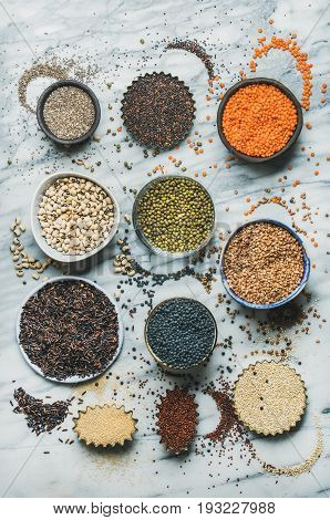 Variety of raw uncooked grains, beans, cereals in bowls, cups and baking molds for healthy cooking over marble background, top view. Clean eating, healthy, detox, vegan, diet, vegetarian food concept