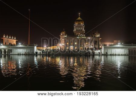 Night view of one of the main Sikh shrines of Delhi - Gurudwara Bangla Sahib. The main building of the temple is illuminated and is reflected in Sarowar pond water.
