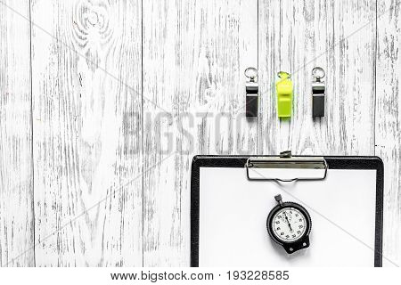 To judge competition. Stopwatch, whistle, pad on wooden table background top view copyspace.