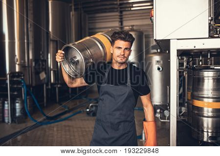 Male Brewer Carrying Metal Container At Brewery Factory