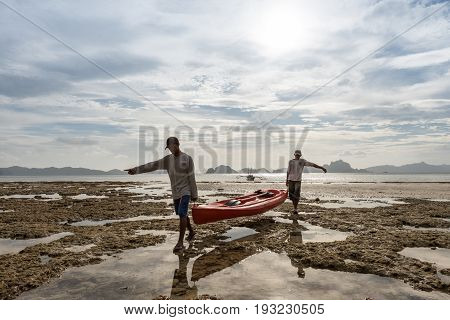 EL NIDO, PALAWAN, PHILIPPINES - MARCH 29, 2017: Men holding a kayak and their images making reflex on the water at Las Cabanas Beach.