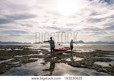 EL NIDO, PALAWAN, PHILIPPINES - MARCH 29, 2017: Wide angle view of two men carrying a kayak from the water to the beach at Las Cabanas Beach.