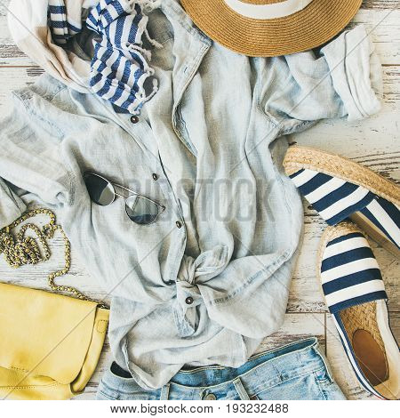 Summer outfit flatlay. Pastel coloured summer women's clothing, parquet background, top view, square crop. Blue shorts, linen shirt, straw hat, yellow bag, sunglasses, striped neckerchief, espadrillas