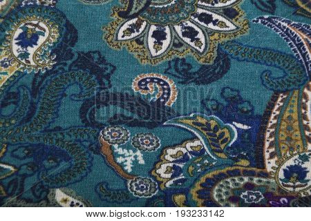 Woolen knitwear fabric with multicolored bright floral paisley pattern in green, yellow and blue colors.
