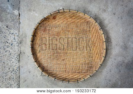 winnowing basket, bamboo threshing basket use for food airing on cement floor background