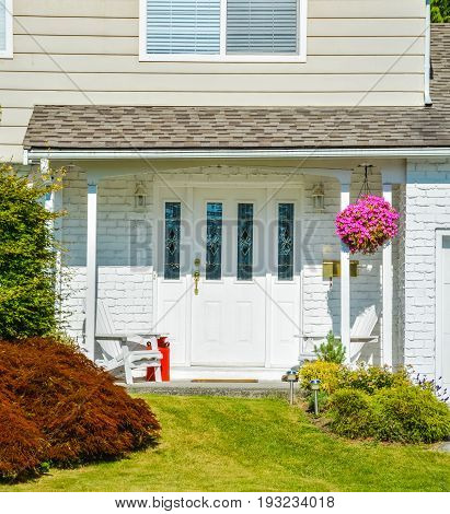 Entrance of residential house decorated with basket of pink flowers two white chairs and red churn
