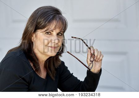 Middle Aged Woman Smiling While Holding Reading Glasses