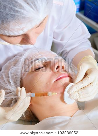 Beautician conducts a session of Mesotherapy injections in the face.