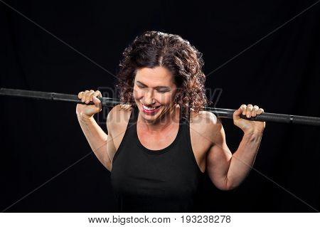 A female weight lifter holding a barbell on her shoulders laughs with eyes closed. She looks like she is pushing through a hard set of backsquats.