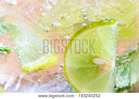 Close up concept on piece of lemon or lime in lemonade for wallpaper or background. Half-circle of lemon or lime in sparkling water (soda) in natural tone. Water bubble and half-circle lemon or lime.