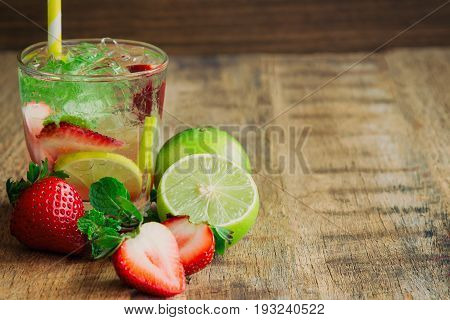 Strawberry lemon lime soda in clear glass on rustic wood table. Homemade beverage strawberry soda ingredients with strawberry lemon or lime sparkling water and mint leaf. Infused water on plank with copy space for background or wallpaper.