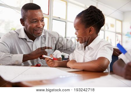 Teacher helping elementary school girl at her desk, close up