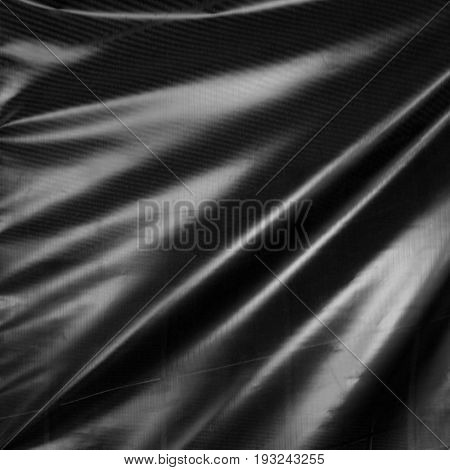 Black drape. Wavy folds of synthetic material. Abstract background.