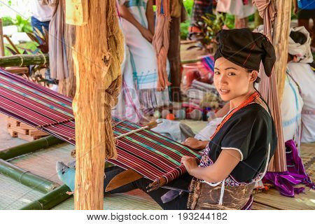CHIANGMAI THAILAND - JANUARY 24 2015: Hill tribe girl demonstrating weaving fabric in 22nd Traditional Skirt Fabric and The Indigenous Product and Culture Festival in Mae Chaem of Chiangmai Thailand