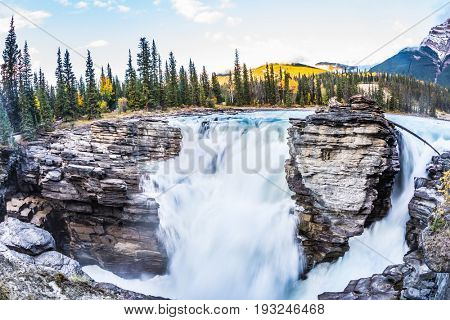 The full-water waterfall of Athabasca. Clear autumn evening in Jasper National Park. Cold blue water at sunset. The concept of extreme and ecological tourism