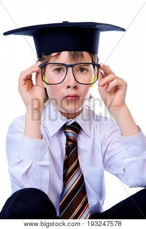 Portrait of a cute student boy in white shirt, a tie and academic hat. Educational concept. Isolated over white.