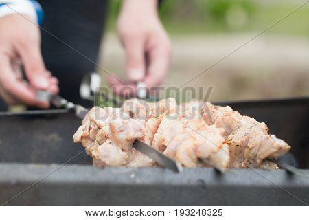 Crude meat on skewers in the course of frying. Male hands close up hold skewers. Skewers with meat lie on a brazier