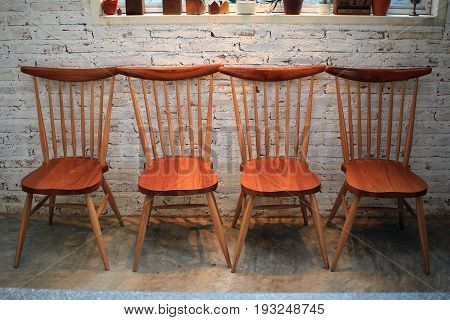 Wooden chairs in room with brick wall