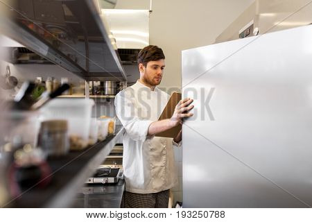 cooking, profession and people concept - male chef cook with clipboard doing inventory in restaurant kitchen fridge