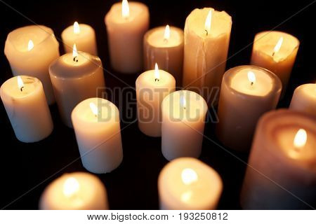 mourning and commemoration concept - candles burning in darkness over black background