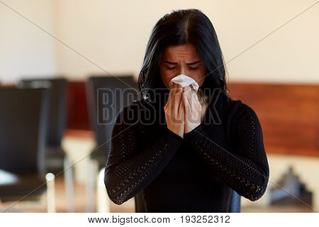 people, grief and mourning concept - crying woman with wipe at funeral in church