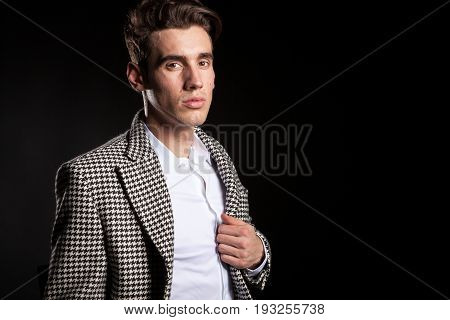 Handsome executive CEO in suit on black background in studio photo. Succesful fashionable businessman