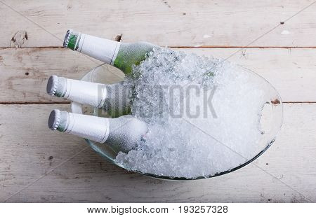 Three frozen glass bottles of beer immersed in the ice