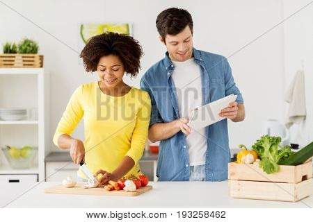 cooking, international and people concept - happy couple with tablet pc computer chopping vegetables at home kitchen