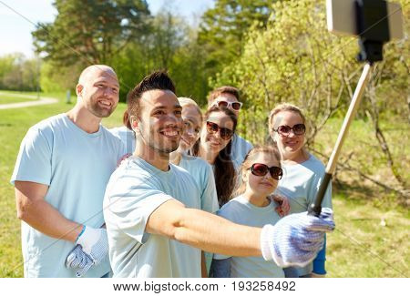 volunteering, charity and people concept - group of happy volunteers taking picture by smartphone and selfie stick in park