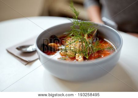 food, new nordic cuisine, culinary and cooking concept - seafood soup with fish and blue mussels in bowl at restaurant
