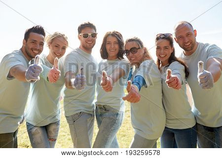 volunteering, charity, people, gesture and ecology concept - group of volunteers showing thumbs up outdoors