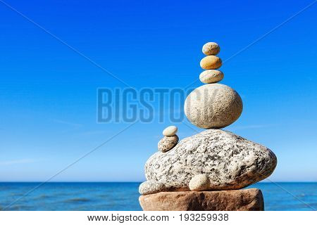 Rock zen pyramid of white and pink stones on a background of blue sky and sea. Concept of balance harmony and meditation