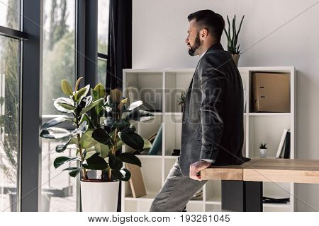 Thoughtful Handsome Businessman In Suit Looking At Window In Modern Office