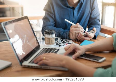 Young hipster worker writing on small notebook while meeting with colleagues in coworking space. Freelancer teamwork and brainstorm concept