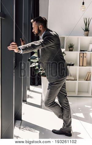 Pensive Bearded Businessman In Suit Looking At Window In Modern Office