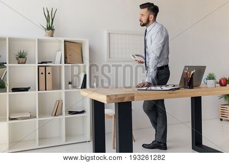 Side View Of Pensive Businessman With Calculator In Hand Standing At Table