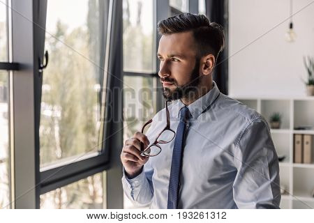 Pensive Bearded Businessman Holding Eyeglasses And Looking At Window In Modern Office