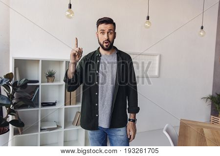 Shocked Bearded Man Pointing Up With Finger And Looking At Camera
