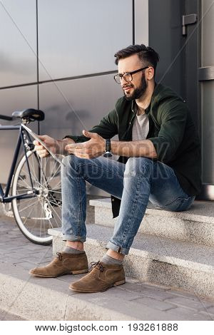 dissatisfied young man using digital tablet while sitting on stairs in city