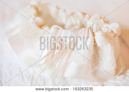Bride's garter. Bride's traditional symbolic accessory. Beige lace with ribbons and rhinestones.