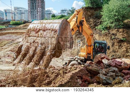 Excavator Performs Excavation Work On The Construction Site. Bucket Closeup.