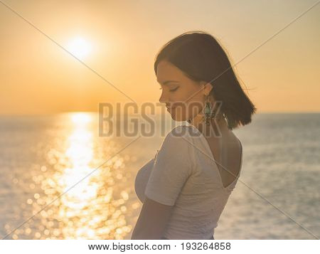 Portrait of young attractive woman standing in morning sunlight close to sea or ocean. Beautiful lady with short brunette hair and long earrings.