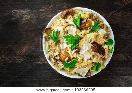 An overhead photo of a mushroom risotto with champignons, fresh parsley, porcini, and Parmesan, on a dark rustic texture with a place for text