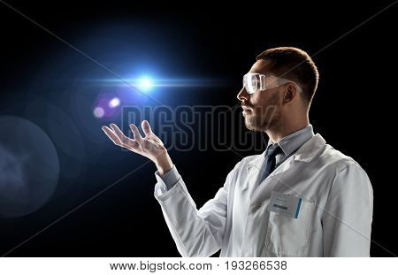 science, future technology and people concept - male doctor or scientist in white lab coat and safety glasses with laser light over black background