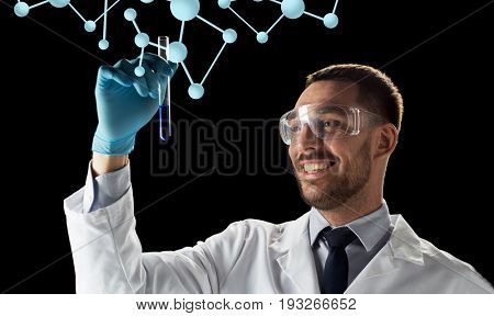 science, biology and people concept - young smiling scientist in safety glasses with test tube and molecules over black background