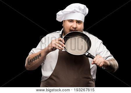 Professional Chef In Hat And Apron Biting Frying Pan Isolated On Black