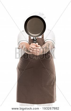 chef covering face with frying pan in hands isolated on white