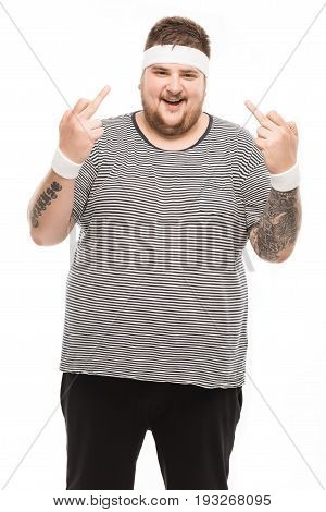 Young Smiling Man Showing Middle Finger Sign And Looking At Camera Isolated On White