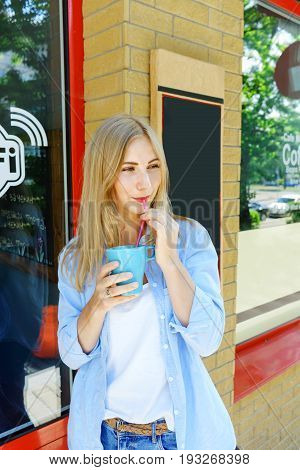 Attractive young girl drinking coffee. Jeans wear and pretty blonde hair.